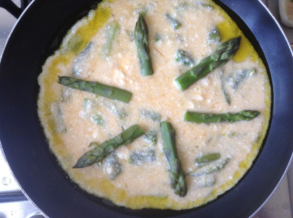 In una padella riscalda l'olio, disponi le teste degli asparagi e versaci lo sbattuto d'uovo sopra